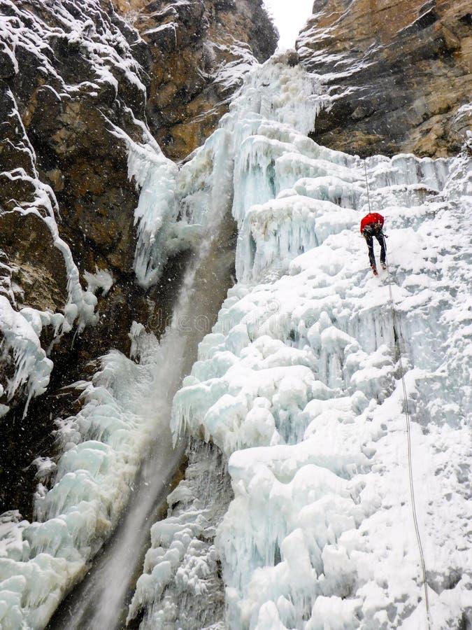 Mannelijke ijsklimmer in een rood jasje die van een gevaarlijke instortende het ijsdaling van Nd rappelling in de diepe winter royalty-vrije stock fotografie