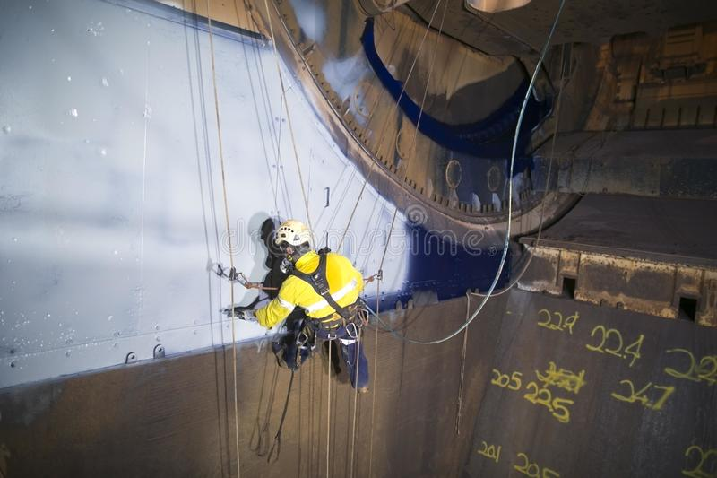 Mannelijke industriële de technicusschilder die van de kabeltoegang bij hoogte het hangen aan tweelingkabels werken stock foto