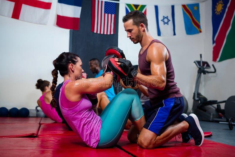 Mannelijke instructeur die vrouwelijke bokser bijstaan royalty-vrije stock foto