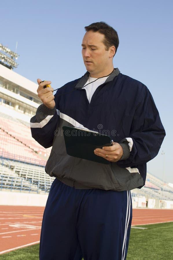 Mannelijke Instructeur Looking At Stopwatch stock foto