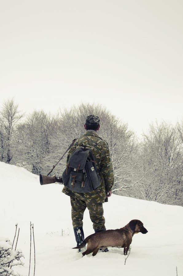 Mannelijke jager met een hond in het bos in de winter royalty-vrije stock afbeelding