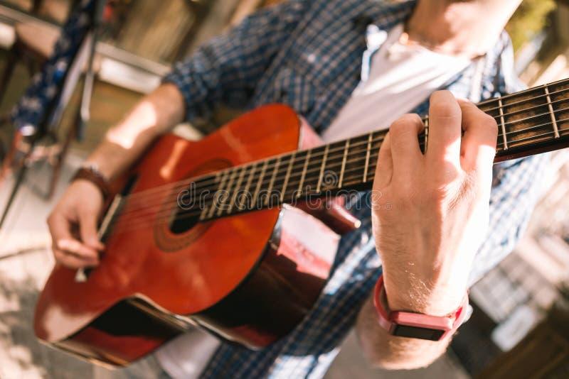 Mannelijke jonge gitarist die juiste gitarenpraktijk selecteren stock afbeeldingen