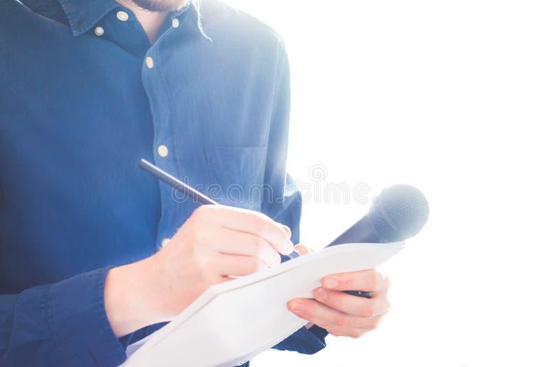 Mannelijke journalist bij persconferentie die, die microfoon houdt en nota's neemt stock fotografie