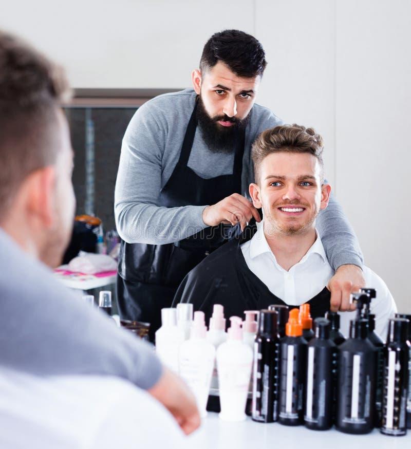 Mannelijke kapper die cliënt voor kapsel voorbereiden stock fotografie