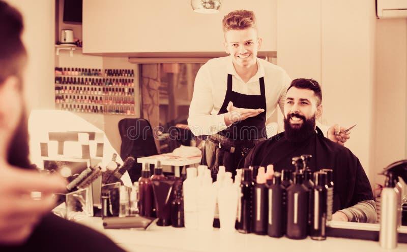 Mannelijke kapper die resulterend kapsel tonen aan cliënt bij haarzout royalty-vrije stock afbeeldingen