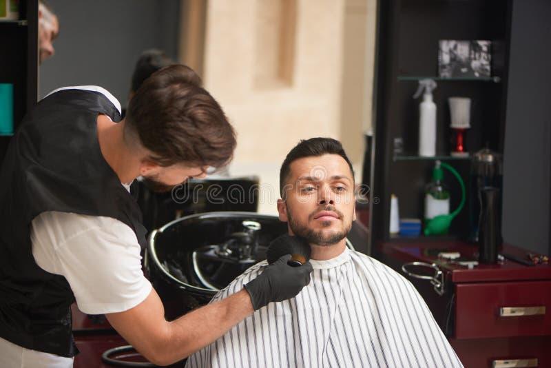Mannelijke kapper het verzorgen cliënt` s baard met borstel royalty-vrije stock foto's