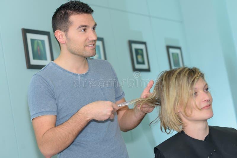 Mannelijke kapper met vrouwelijke klant in haar-salon stock fotografie