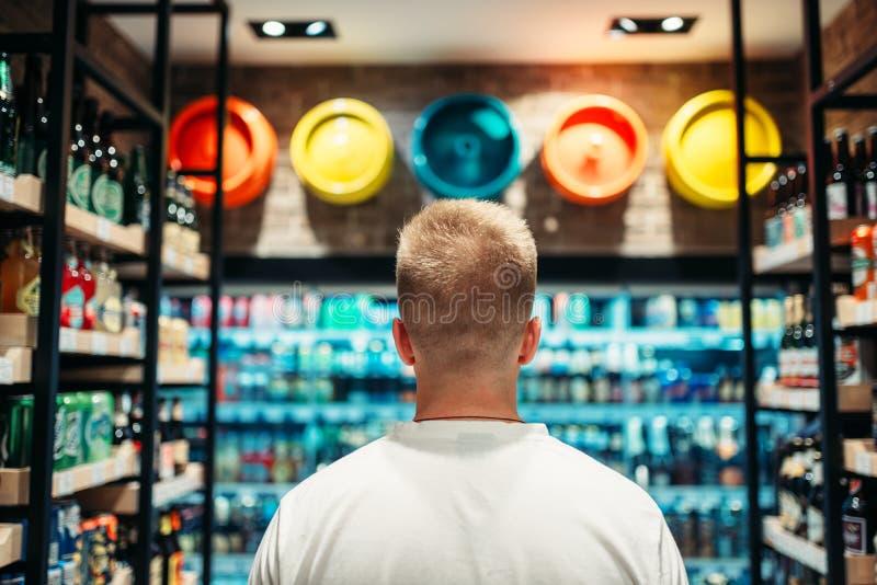 Mannelijke klant die dranken in supermarkt kiezen royalty-vrije stock afbeeldingen