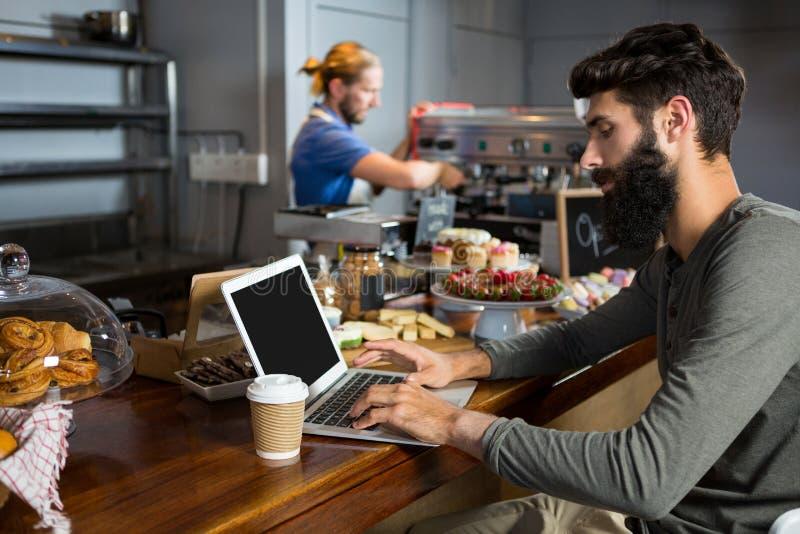 Mannelijke klant die laptop met behulp van terwijl het hebben van koffie bij teller royalty-vrije stock foto's