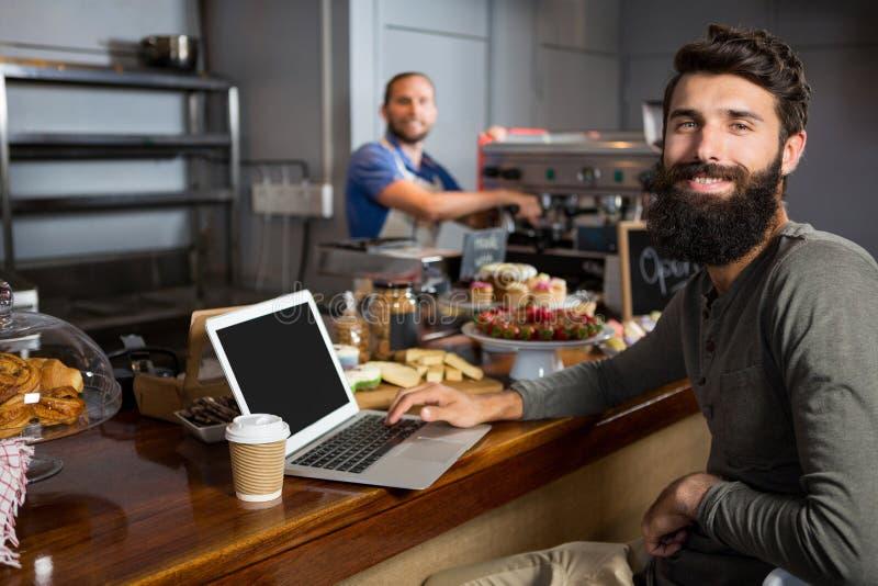 Mannelijke klant die laptop met behulp van terwijl het hebben van koffie bij teller in koffiewinkel stock foto