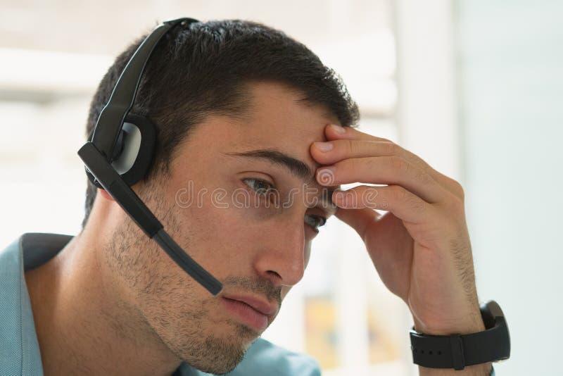 Mannelijke klantenservicestafmedewerker met hoofdtelefoonzitting bij bureau in bureau stock foto
