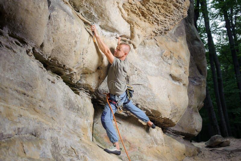 Mannelijke klimmer die grote kei in aard met kabel beklimmen stock afbeeldingen