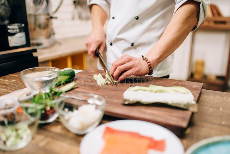 Mannelijke kokhanden die sushibroodjes, zeevruchten maken royalty-vrije stock foto's