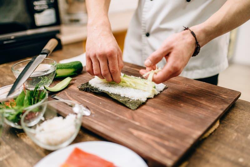 Mannelijke kokhanden die sushibroodjes, zeevruchten maken stock foto's