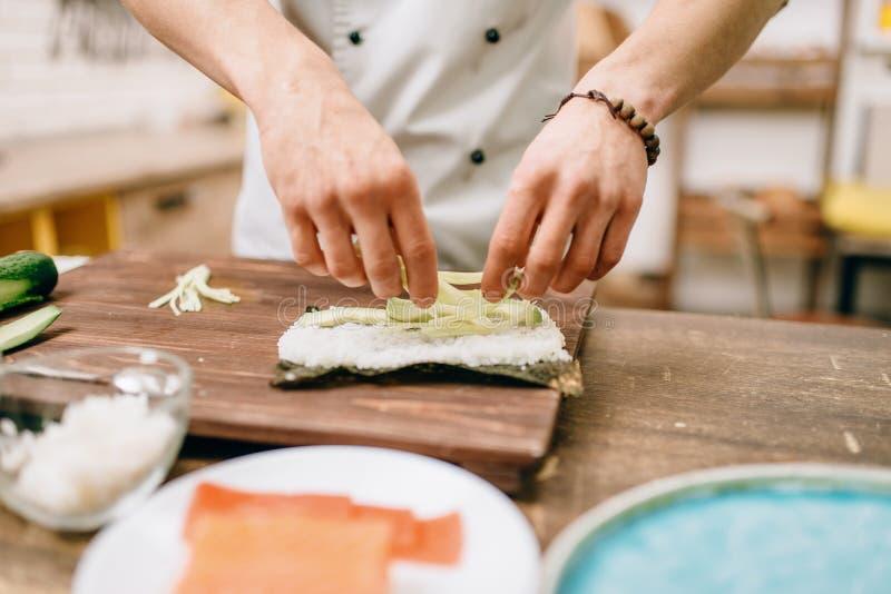 Mannelijke kokhanden die sushibroodjes, zeevruchten maken royalty-vrije stock afbeeldingen