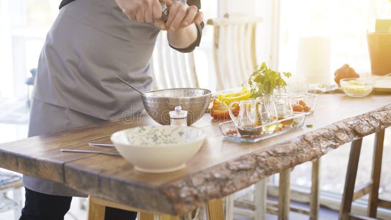 Mannelijke kooktoestel` s handen die peper toevoegen aan een salade stock afbeeldingen