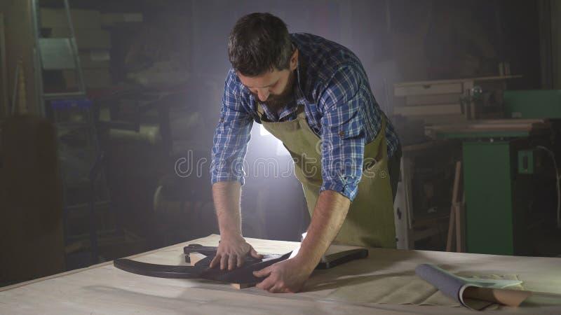 Mannelijke kraftman met een baard in een donkere workshop met een steekproef van leer voor het maken van meubilair stock afbeelding