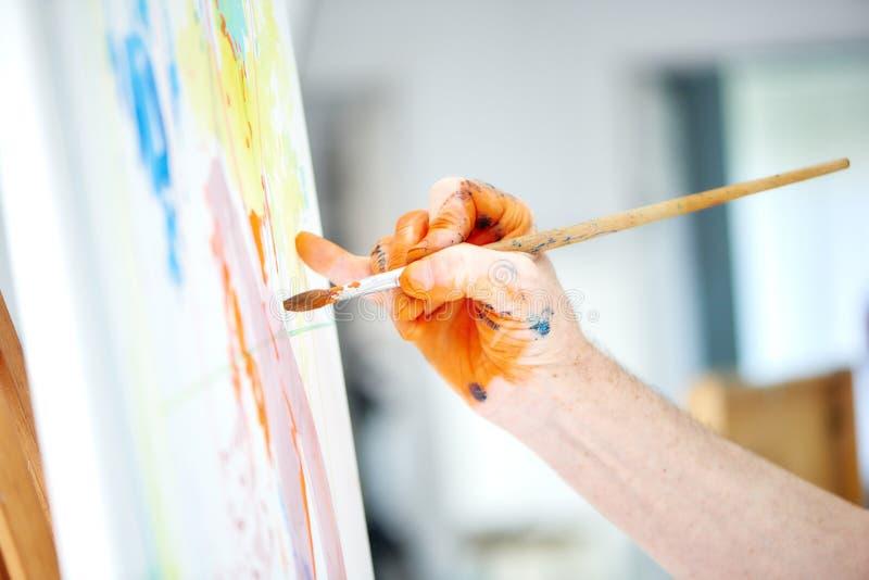 Mannelijke kunstenaarshand die, die borstel houden en rijke oranje verf schilderen royalty-vrije stock foto's