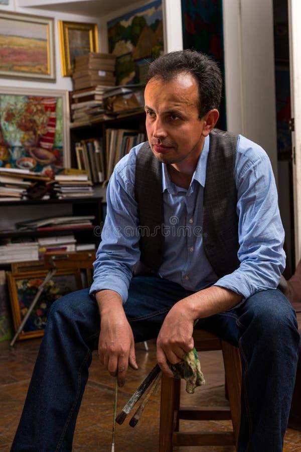 Mannelijke kunstenaarszitting die in een studio denken royalty-vrije stock fotografie