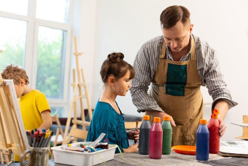 Mannelijke kunstleraar die leuk meisje met kleurrijke verven helpen stock foto