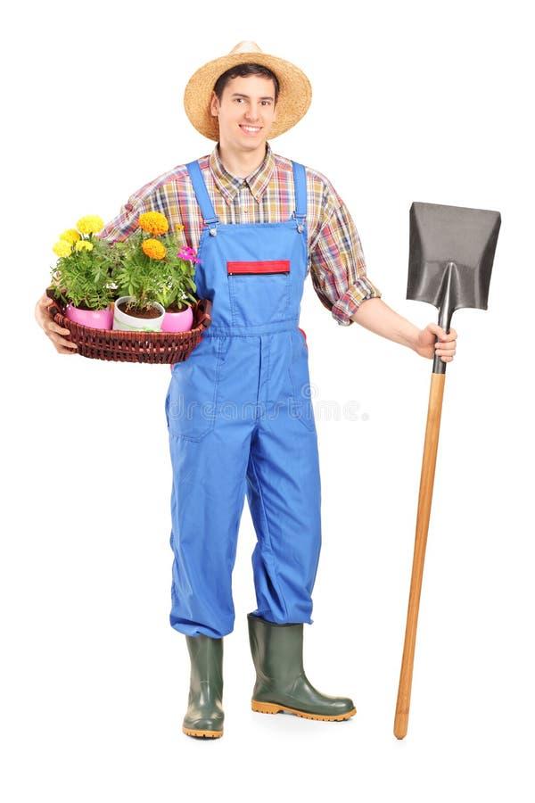 Mannelijke landbouwarbeider die een schop en bloemen houden stock foto