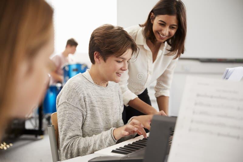 Mannelijke Leerling met de Muziekles van Leraarsplaying piano in stock afbeelding