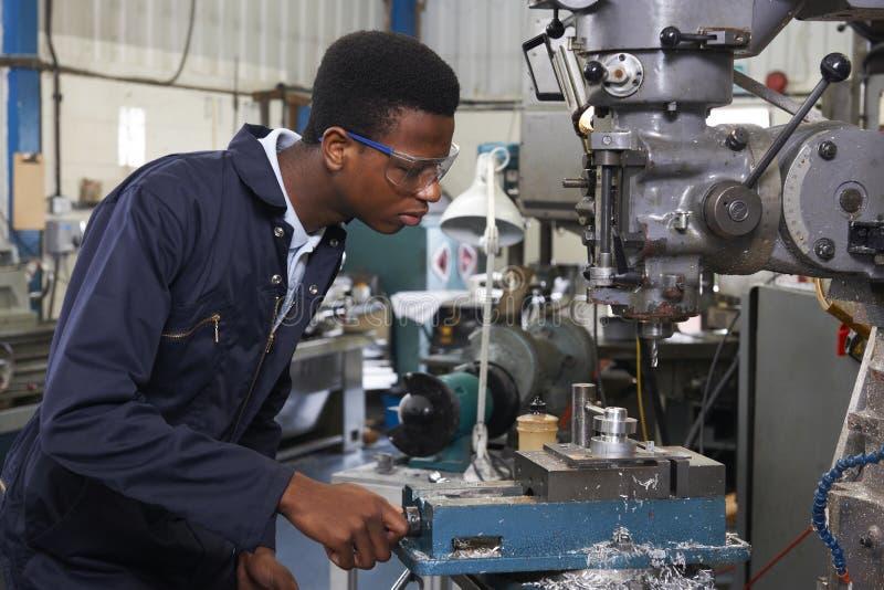 Mannelijke Leerlingsingenieur Working On Drill in Fabriek stock afbeelding