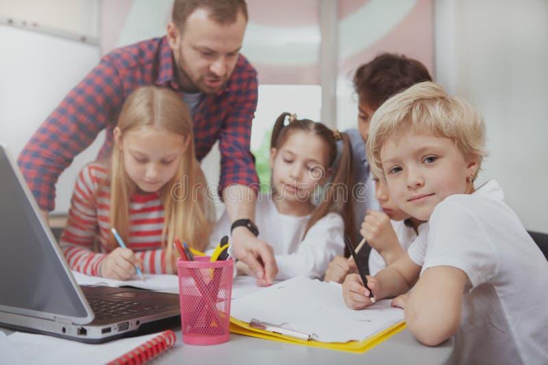 Mannelijke leraar die met kinderen bij kleuterschool werken stock fotografie