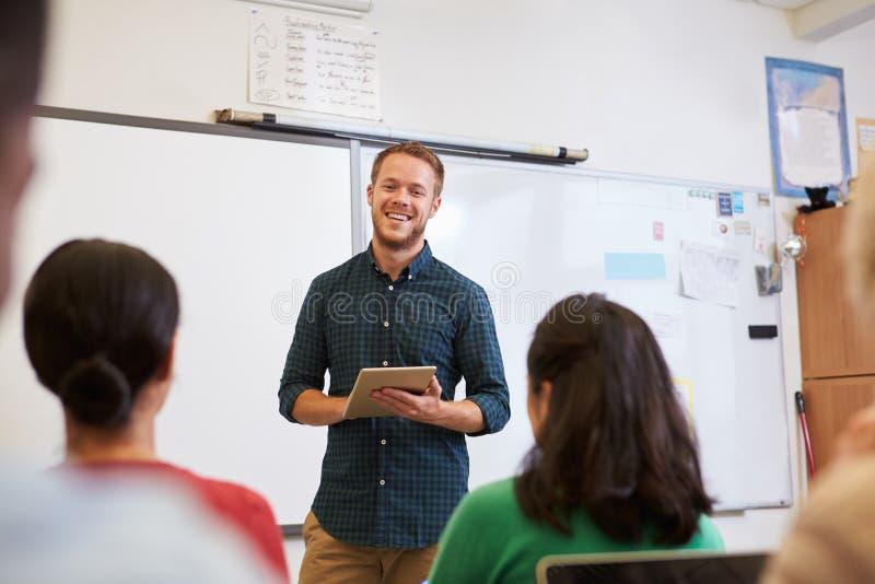 Mannelijke leraar die tabletcomputer met behulp van bij volwassenenvormingsklasse