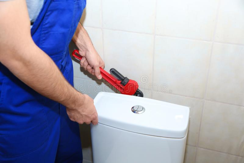 Mannelijke loodgieter die toilettank in badkamers herstellen stock afbeelding