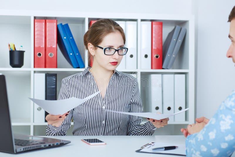 Mannelijke manager die aan emotionele vrouwelijke chef- holdingsdocumenten luisteren, die op documenten richten Geschil of argume royalty-vrije stock fotografie