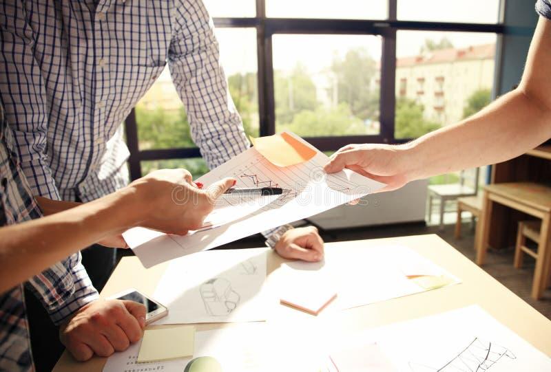 Mannelijke manager zijn ideeën zetten en businessplan schrijven op het werk, de pennen van de mensenholding en documenten die, di royalty-vrije stock foto