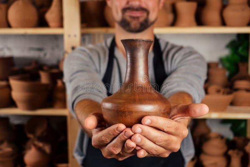 Mannelijke master potter in apron sculpt een diepe kom bruine klei op het wiel van een Potter In de workshop op de achtergrond royalty-vrije stock foto's