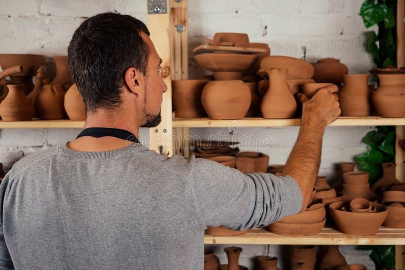 Mannelijke master potter in apron sculpt een diepe kom bruine klei op het wiel van een Potter In de workshop op de achtergrond royalty-vrije stock afbeelding