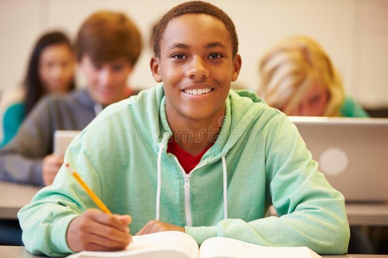 Mannelijke Middelbare schoolstudent Studying At Desk in Klaslokaal stock foto
