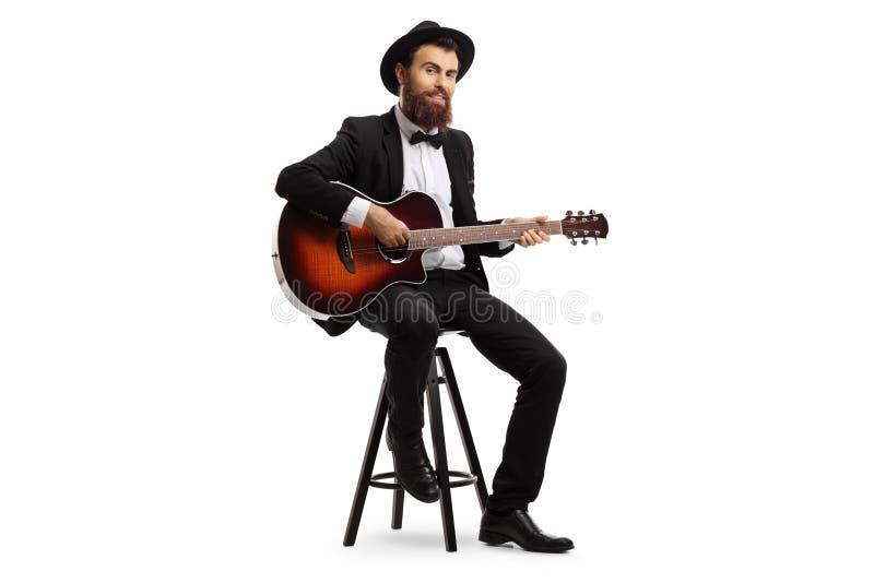 Mannelijke musicus die en een akoestische gitaar zitten spelen stock afbeelding