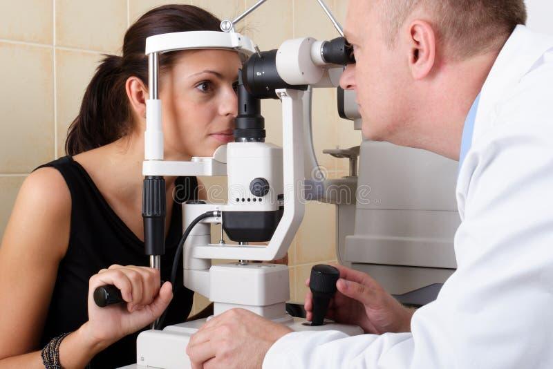 Mannelijke oftalmoloog die een oogonderzoek leidt stock afbeelding