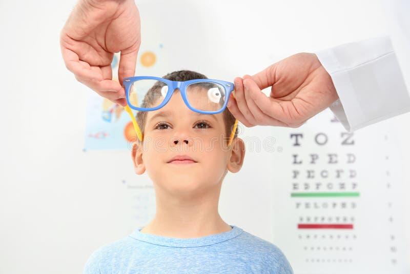 Mannelijke oftalmoloog die glazen op weinig jongen zetten stock foto