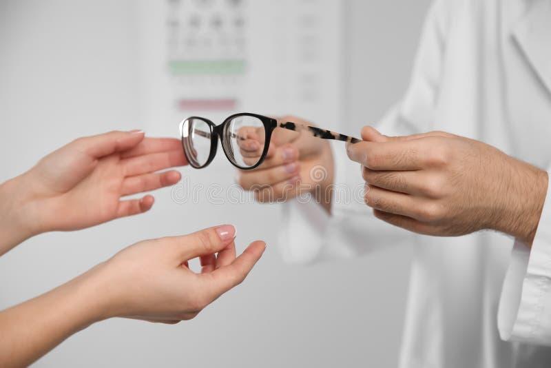Mannelijke oftalmoloog die vrouw helpen glazen in kliniek kiezen royalty-vrije stock foto's