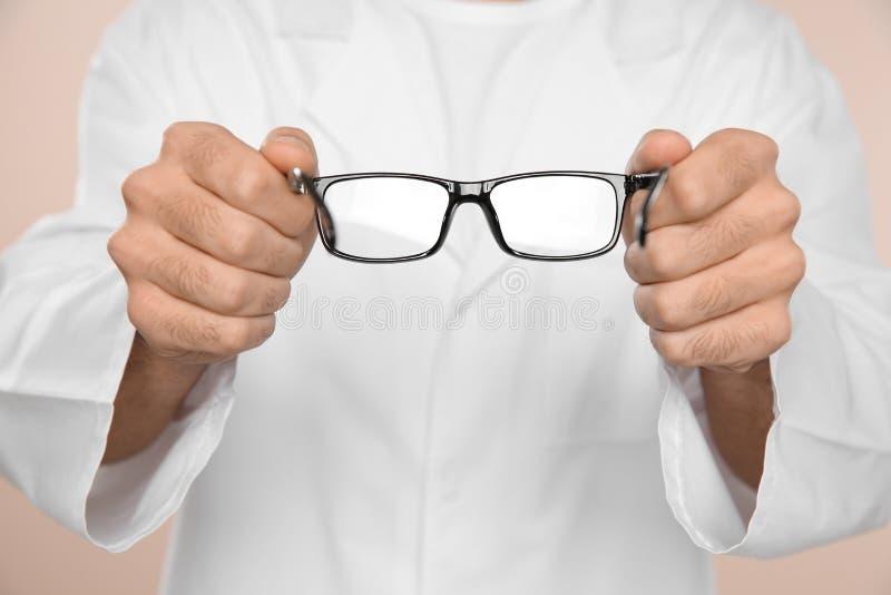 Mannelijke oftalmoloog met oogglazen op lichte achtergrond, close-up royalty-vrije stock afbeelding