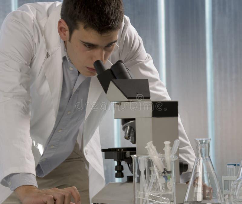 Mannelijke onderzoeker die door een microscoop in a kijkt royalty-vrije stock foto's