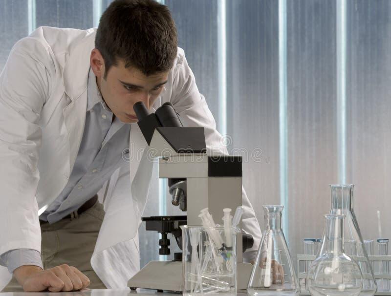 Mannelijke onderzoeker die door een microscoop in a kijkt stock afbeelding