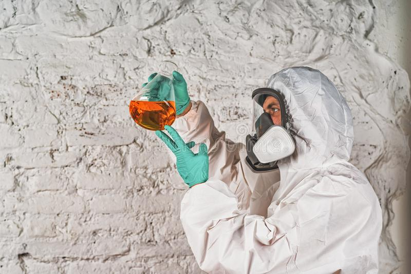 Mannelijke onderzoeker die vloeibare reagens in laboratoriumglaswerk analyseren stock foto's