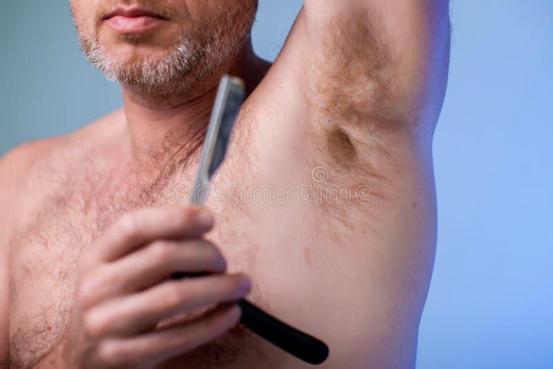 Mannelijke ontharing Jonge aantrekkelijke mens die scheermes met behulp van om haar uit zijn oksel te verwijderen Mensen en bodyc royalty-vrije stock afbeelding