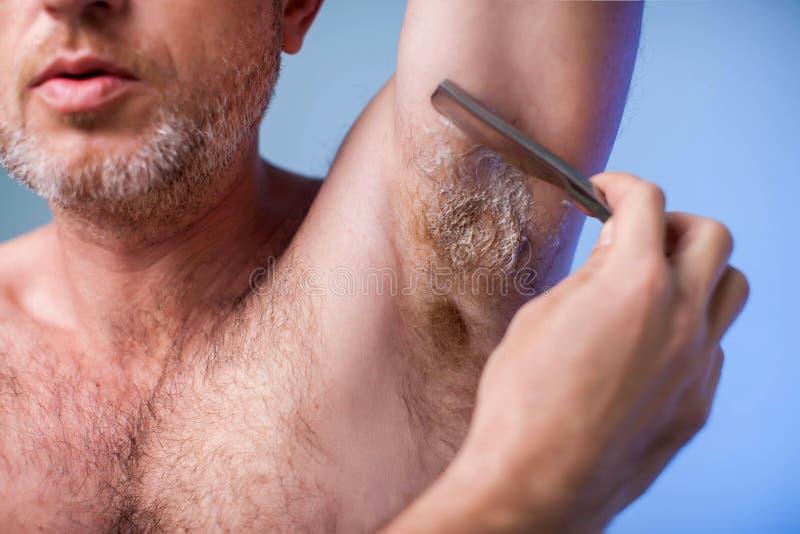 Mannelijke ontharing Jonge aantrekkelijke mens die scheermes met behulp van om haar uit zijn oksel te verwijderen Mensen en bodyc stock foto