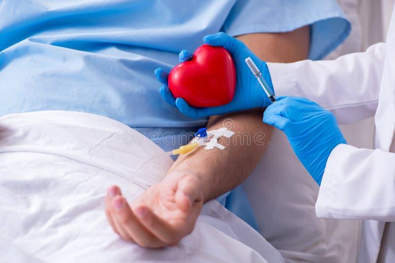 Mannelijke patiënt die bloedtransfusie in het ziekenhuiskliniek krijgen stock afbeeldingen
