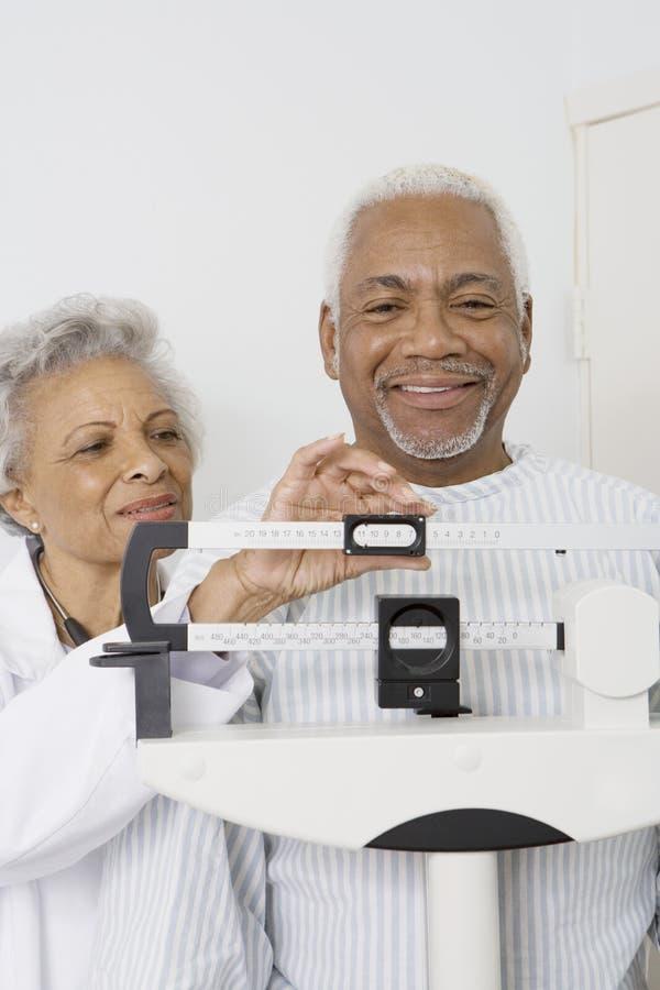 Mannelijke Patiënt die Gewicht met Arts Assisting Him meten stock afbeeldingen