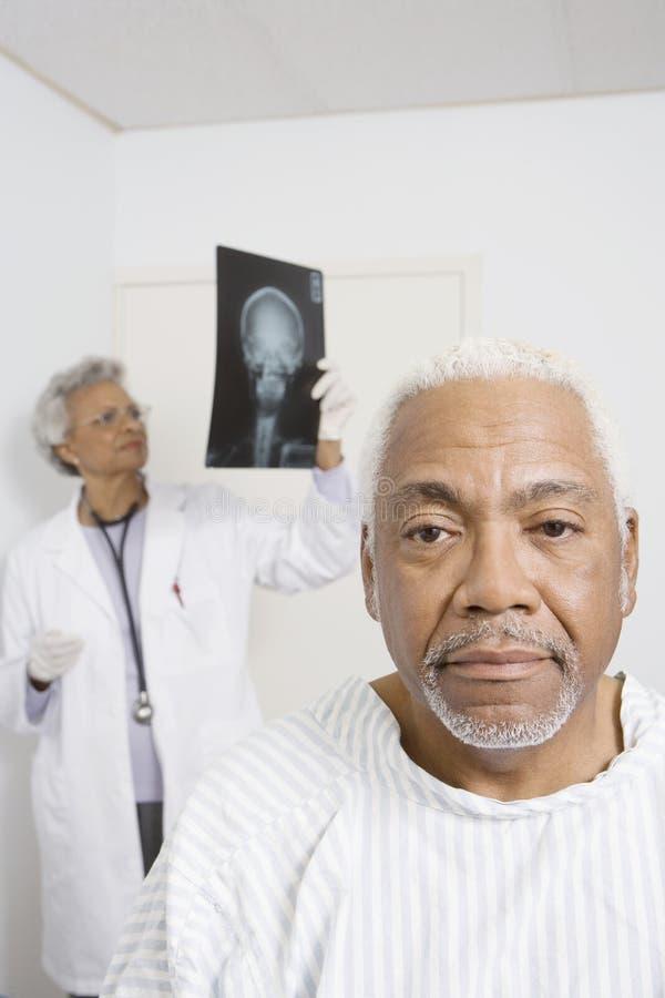 Mannelijke Patiënt met de Röntgenstraal van ArtsenExamining op Achtergrond royalty-vrije stock afbeelding