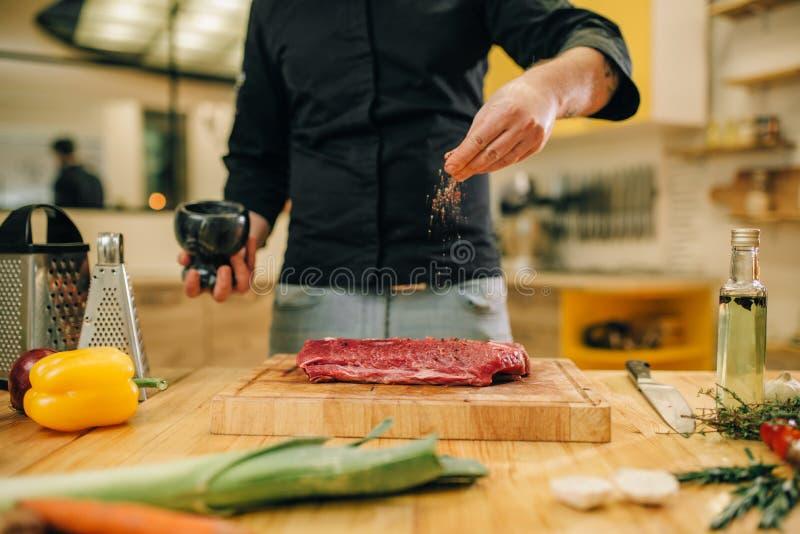 Mannelijke persoon die ruw vlees op houten raad marineren stock afbeelding