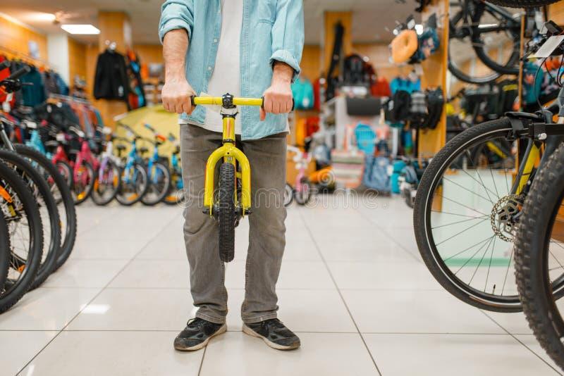 Mannelijke persoon met de fiets van kinderen, sportenwinkel stock afbeeldingen